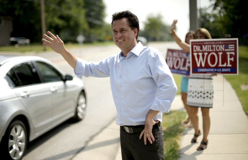 Milton Wolf, a Republican candidate for the U.S. Senate in Kansas, waves to motorists outside a polling place on primary election day, Tuesday, Aug. 5, 2014, in Overland Park, Kan. Tea party-backed Wolf is challenging incumbent Sen. Pat Roberts. (AP Photo/Charlie Riedel)