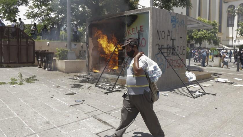 Un cajero automático con billetera digital Chivo, que intercambia efectivo por criptomonedas Bitcoin, es incendiada durante una protesta contra el presidente Nayib Bukele en San Salvador, El Salvador, el miércoles 15 de septiembre de 2021. (AP Foto/Iván Manzano)