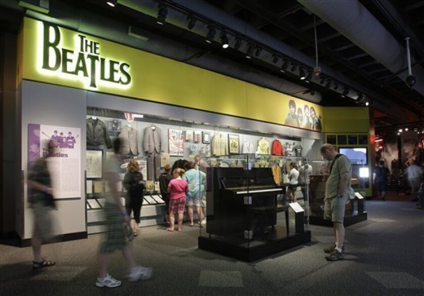 In this June 7, 2011 photo, visitors view an exhibit on The Beatles, at the Rock and Roll Hall of Fame and Museum in Cleveland. The Rock Hall says the exhibit is the world's largest collection of items from the group, as part of a redesign. (AP Photo/Mark Duncan)