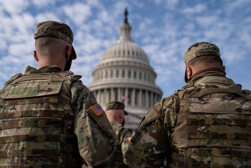 Members of the National Guard in the plaza in front of the U.S. Capitol building.