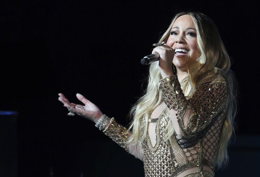 Mariah Carey sings into a microphone.