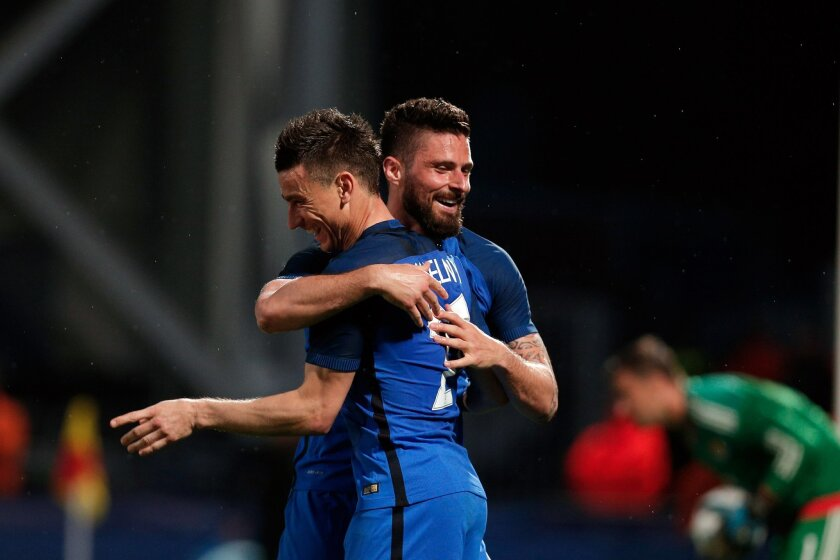 France's Laurent Koscielny, left, celebrates with teammate France's Olivier Giroud, after he scored a goal during the friendly soccer match between France and Scotland at the Saint Symphorien Stadium in Metz, eastern France, Saturday, June 4, 2016. The French squad is in preparation for the EURO 20