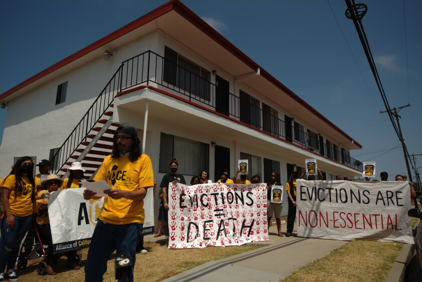 Tenants and tenants' rights advocates hold a rally against evictions on July 15 outside a Chula Vista apartment.