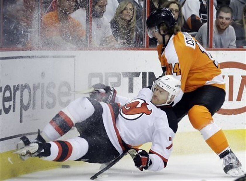New Jersey Devils' Henrik Tallinder (7), of Sweden, is knocked to the ice by Philadelphia Flyers' Sean Couturier (14) during the second period of an NHL hockey game, Thursday, April 18, 2013, in Philadelphia. (AP Photo/Matt Slocum)