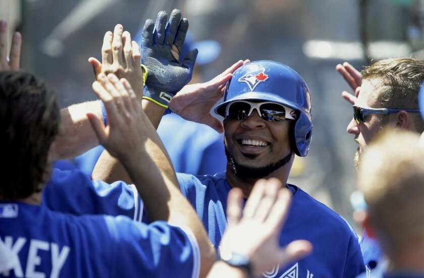 Toronto Blue Jays' Edwin Encarnacion, center, gets congratulations from teammates after scoring on an infield single by Ben Revere during the third inning of a baseball game against the Los Angeles Angels in Anaheim, Calif., Sunday, Aug. 23, 2015. (AP Photo/Alex Gallardo)