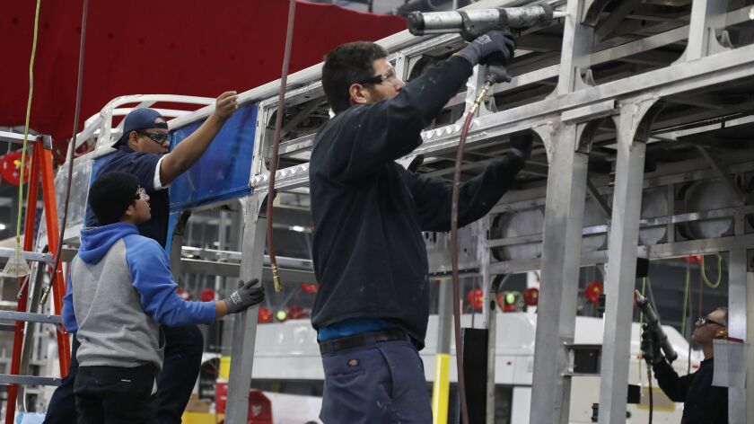 Workers build an electric bus at the BYD production facility in Lancaster this year. California gained a net 6,600 manufacturing jobs in October.