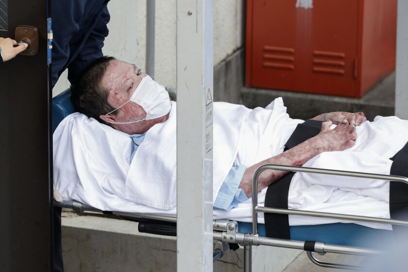 Shinji Aoba on a stretcher is carried to Fushimi police station May 27 after being arrested in Kyoto, western Japan.