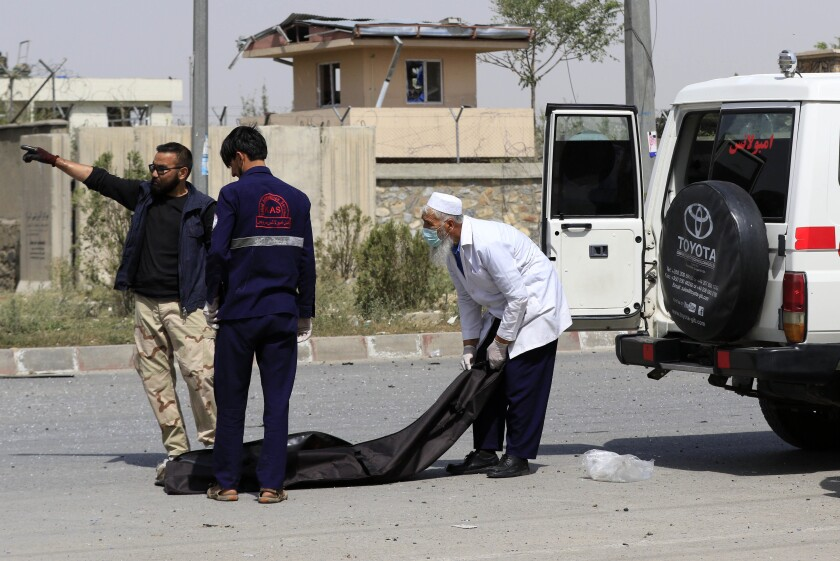 Afghan security officials move the body of an alleged suicide bomber on Aug. 7.