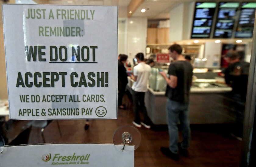 A sign at a Vietnamese restaurant in San Francisco in 2019 explains its no-cash policy. San Francisco is one of several cities in the United States that now require brick-and-mortar retailers to accept cash payments.