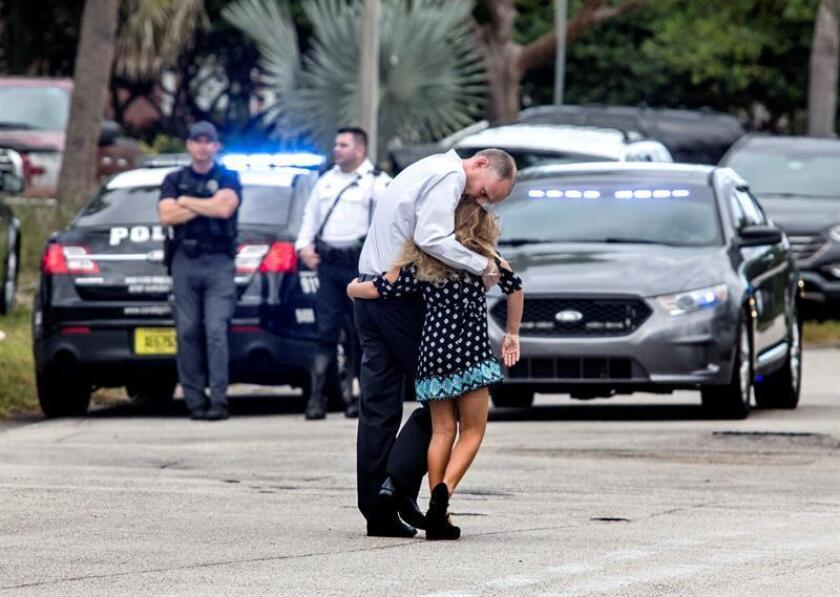 Un hombre consuela a una niña después de asistir a los preparativos del funeral de Gina Montalto en el Kraeer Funeral Home en Coral Springs, Florida, (EE.UU.). EFE/Archivo
