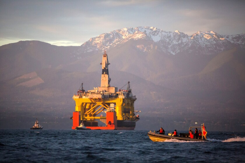 A small boat crosses in front of an oil drilling rig as it arrives in Port Angeles, Wash., aboard a transport ship after traveling across the Pacific on April 17, 2015.