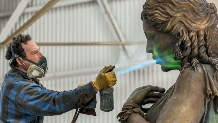 Patina specialist Karl Reichley works on the Hecuba statue for the USC Village at Artworks Foundry i