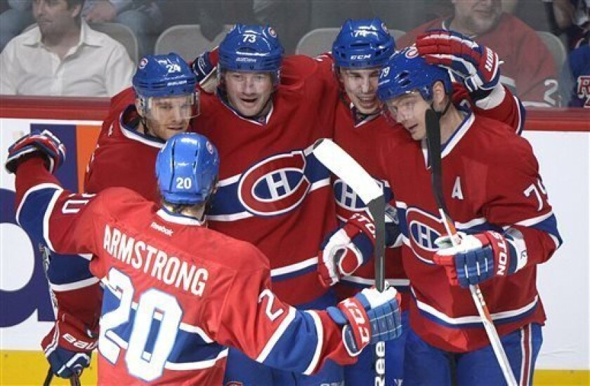 Montreal Canadiens' Michael Ryder (73) celebrates with teammates Jeff Halpern (24), Colby Armstrong (20), Alexei Emelin (74) and Andrei Markov (79) after scoring against the New York Rangers during first-period NHL hockey game action in Montreal, Saturday, March 30, 2013. (AP Photo/The Canadian Pre