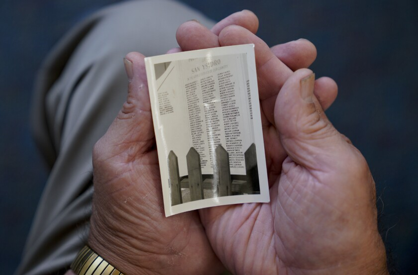 Charlie Velazquez, 86, holds a photo that he inherited from his father. The wallet size photo shows the original plaque that displayed the 147 names of men and women from San Ysidro who served in World War II, including the name of his two brothers, Alfredo and Adolfo who served in the U.S. Army.