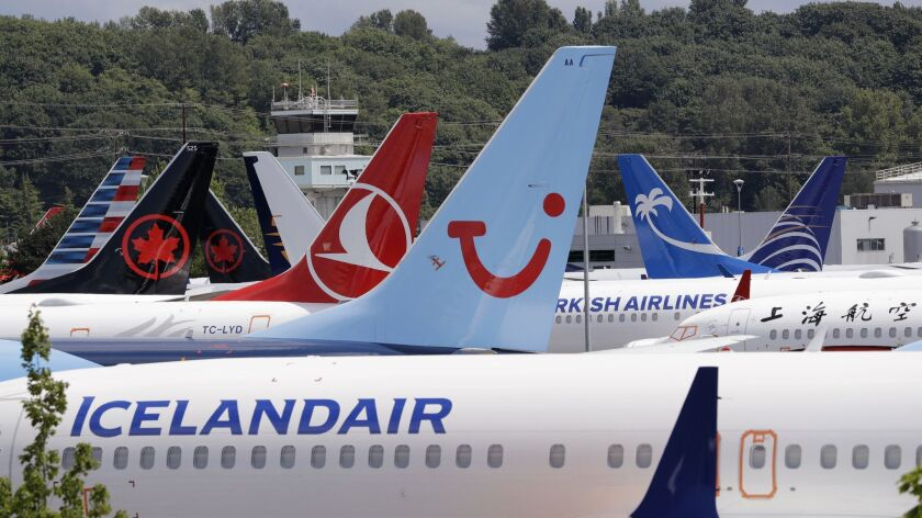 Dozens of grounded Boeing 737 MAX airplanes crowd a parking area adjacent to Boeing Field Thursday,