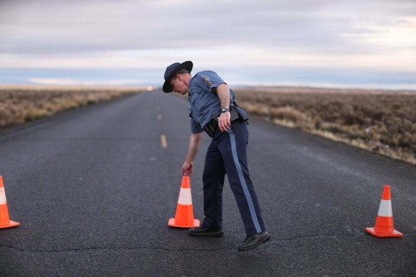 An officer with the Oregon State Police moves a cone to establish a roadblock along one of the routes to the Malheur National Wildlife Refuge in Harney County, Ore., Jan. 28, 2016. (Beth Nakamura/The Oregonian via AP) MANDATORY CREDIT