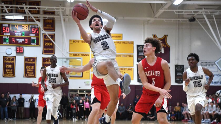 Scotty Pippen Jr. of Chatsworth Sierra Canyon drives to the basket against Devin Askew of Santa Ana Mater Dei in the third quarter of the Southern California Regional Open Division title game Tuesday at Simi Valley High.