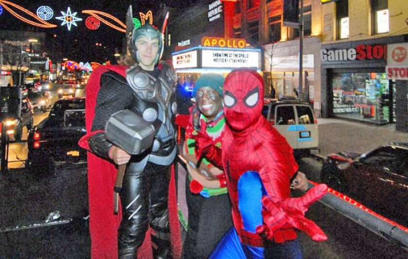 With Harlem's iconic Apollo Theatre as a backdrop, costumed superheroes took part in last year's Harlem Holiday Lights parade.