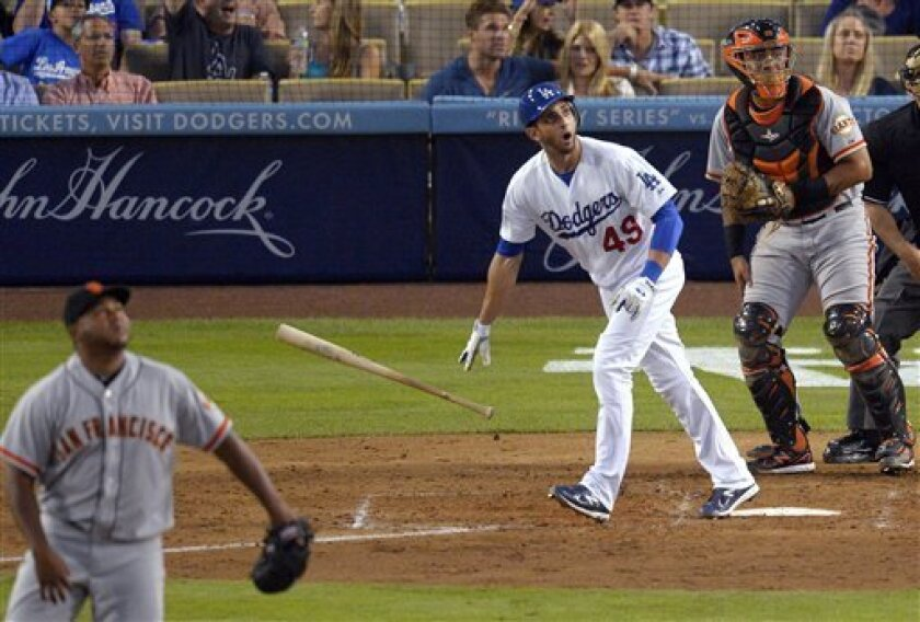 Los Angeles Dodgers' Alex Castellanos, center, watches his solo home run off San Francisco Giants relief pitcher Jean Machi, left, during the eighth inning of a baseball game, Wednesday, Oct. 3, 2012, in Los Angeles. At right is Giants catcher Buster Posey. (AP Photo/Mark J. Terrill)