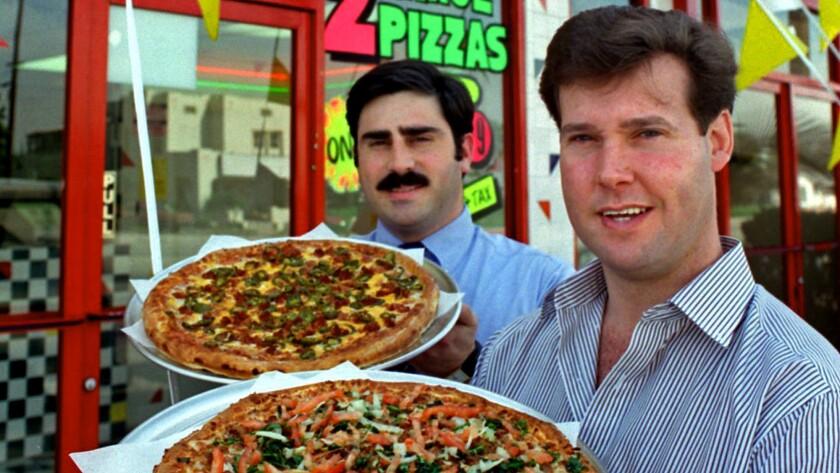 "Alex Meruelo, owner of the La Pizza Loca chain holds a ""Carnitas"" pizza and Tony Tavantzis, franchis"