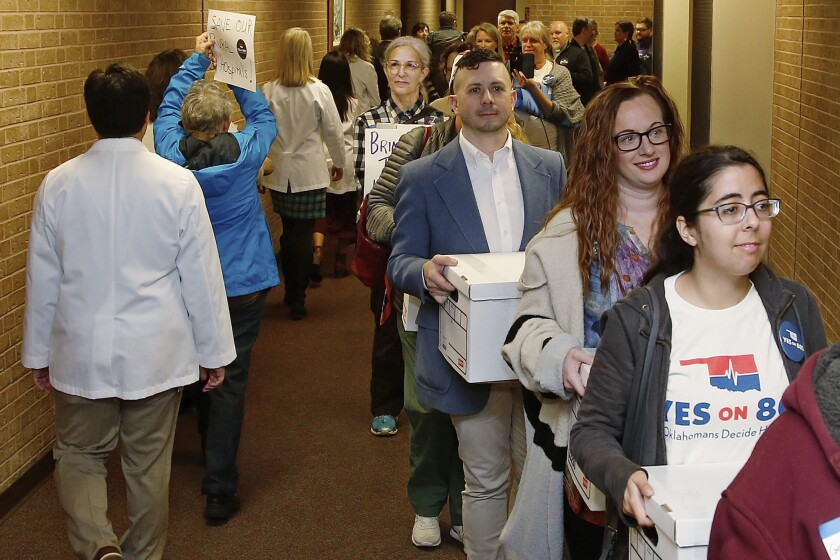 FILE - In this Oct. 24, 2019, file photo, supporters of Yes on 802 Oklahomans Decide Healthcare, calling for Medicaid expansion to be put on the ballot, carry boxes of petitions into the office of the Oklahoma Secretary of State in Oklahoma City. Oklahoma voters will decide Tuesday, June 30, 2020, whether to expand Medicaid to tens of thousands of low-income residents and become the first state to amend their Constitution to do so. (AP Photo/Sue Ogrocki, File)
