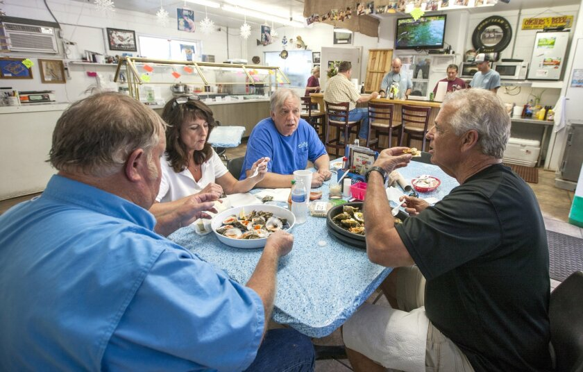 In this Thursday, April 2, 2015 photo, from left, Charles Pennycuff, Sue Gladski, Joe Gladski and Mike Thornburg enjoy fresh shucked Apalachicola oysters at Lynn's Quality Oysters in Eastpoint, Fla. The local oyster industry in Apalachicola is under threat from water-flow issues, environmental concerns, health and safety regulations and economic realities. Apalachicola-based oyster houses have either stopped selling to restaurants on the wholesale market or have opted to supplement their supply with oysters from Texas and Louisiana. (AP Photo/Mark Wallheiser)