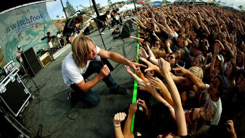 Jon Foreman (crouching) and Switchfoot have been holding their Bro-Am at Moonlight Beach in Encinitas since 2005. The combination concert and surf contest has raised $1.5 million for various charities.
