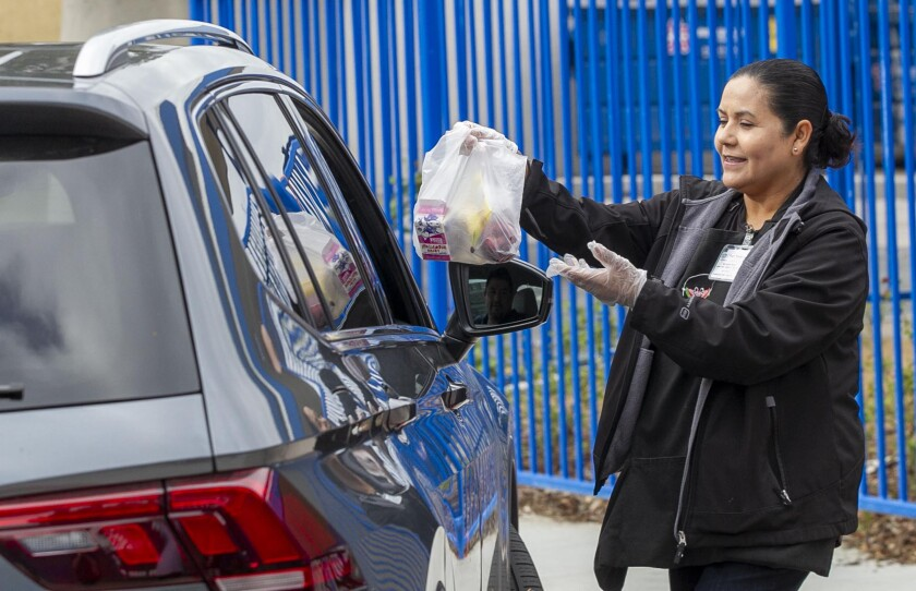 Maggie Meza, lead child nutrition specialist, hands a grab-and-go breakfast bag to a waiting car at La Mirada Elementary School, part of the San Ysidro School District, on March 16, 2020, the first day of school closures under the COVID-19 virus school shutdown.
