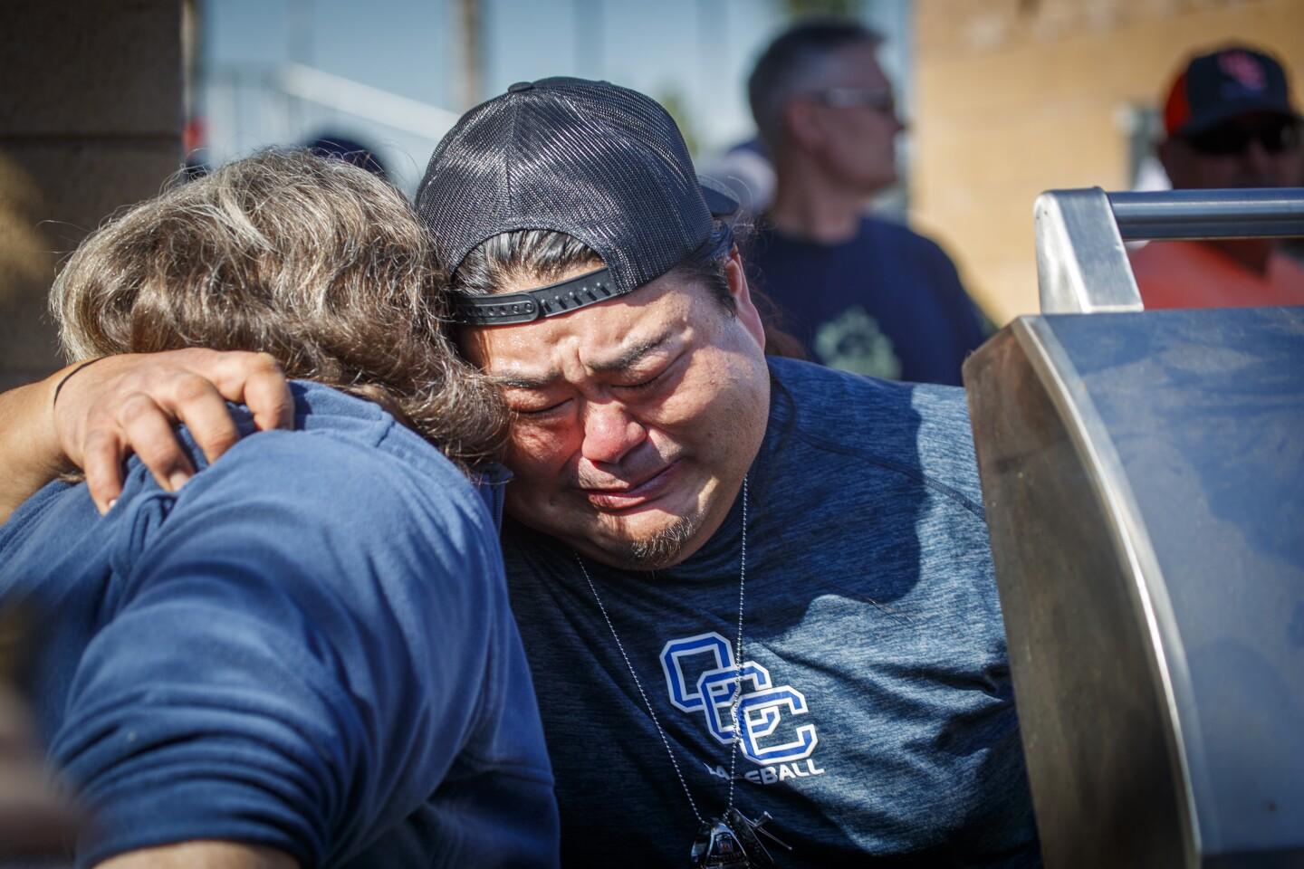 """COSTA MESA, CALIF. -- TUESDAY, JANUARY 28, 2020: Dottie Aper, left, consoles Lee Watanabe, who is mourning coach John Altobelli and who also lost his brother, Jourdan Watanabe, the former Orange Coast College catcher who died in 2009, while cooking food as Orange Coast College baseball team members participate in a short tribute to coach John Altobelli, 56, before a season opener against Chula Vista Southwestern, just two days after longtime Pirates coach Altobelli, his wife, Keri, and their 13-year-old daughter, Alyssa, died in the fiery helicopter crash that also killed former Lakers star Kobe Bryant on Sunday. Speeches by associate head coach Nate Johnson and athletic director Jason Kehler as well as a moment of silence on the Wendell Pickens Field on the school's campus in Costa Mesa, Calif., on Jan. 28, 2020. Altobelli guided the Pirates to four state championships and more than 700 victories in 27 seasons as coach. Last season, Altobelli was named national coach of the year by the American Baseball Coaches Association for leading the Pirates to the state title. OCC sophomore left-handed pitcher Mike Ryhlick started the game with the inscription """"J.A. 14,"""" Altobelli's initials and jersey number, on his cap. the team erected a bright orange banner with the No. 14 and the phrase """"Forever a Pirate"""" on the left-field fence next to the No. 22 banner honoring Jourdan Watanabe, the former OCC catcher who died in 2009. (Allen J. Schaben / Los Angeles Times)"""