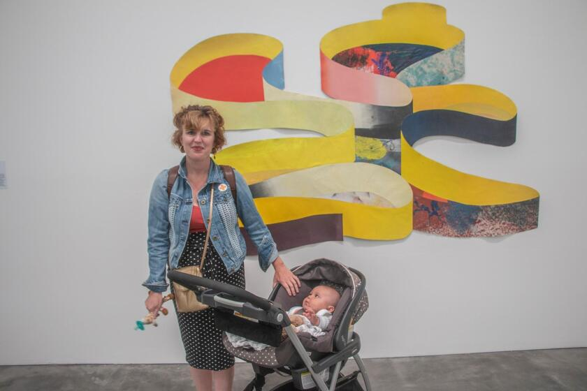 Maura Walters, assistant to the director of La Jolla Athenaeum, with baby James in front of Matt Rich's 'Yellow Ribbon.' Rich, born in Boston, lives and works in San Diego and Los Angeles.