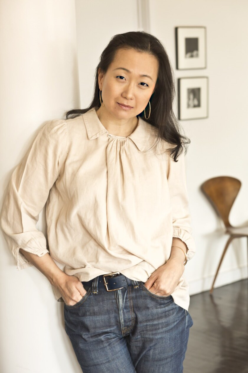 A woman leaning against a wall with her hands in her pants pockets