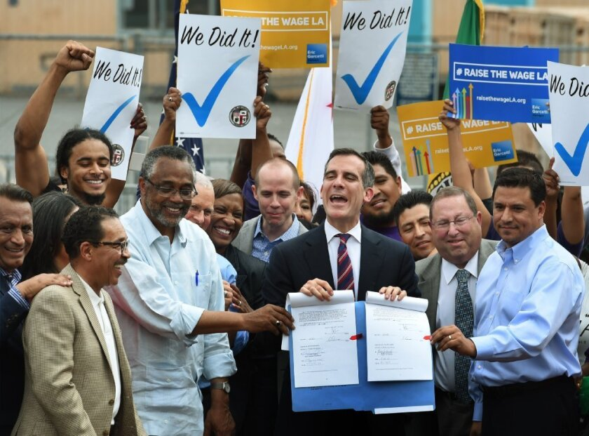 Los Angeles Mayor Eric Garcetti (C) celebrates with City Councilors and labor representatives after he signed into law an ordinance raising the minimum wage to USD 15 an hour by 2020, in Los Angeles, California on June 13, 2015. Los Angeles is the first major city to sign the ordinance and the increase will be USD 6 from the current USD 9 per hour.