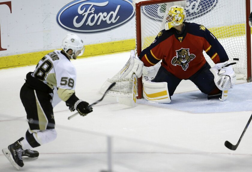 Pittsburgh Penguins defenseman Kris Letang (58) scores the game-winning goal as the puck gets past Florida Panthers goalie Roberto Luongo during overtime in an NHL hockey game, Saturday, Feb. 6, 2016, in Sunrise, Fla. The Penguins defeated the Panthers 3-2 in overtime. (AP Photo/Lynne Sladky)