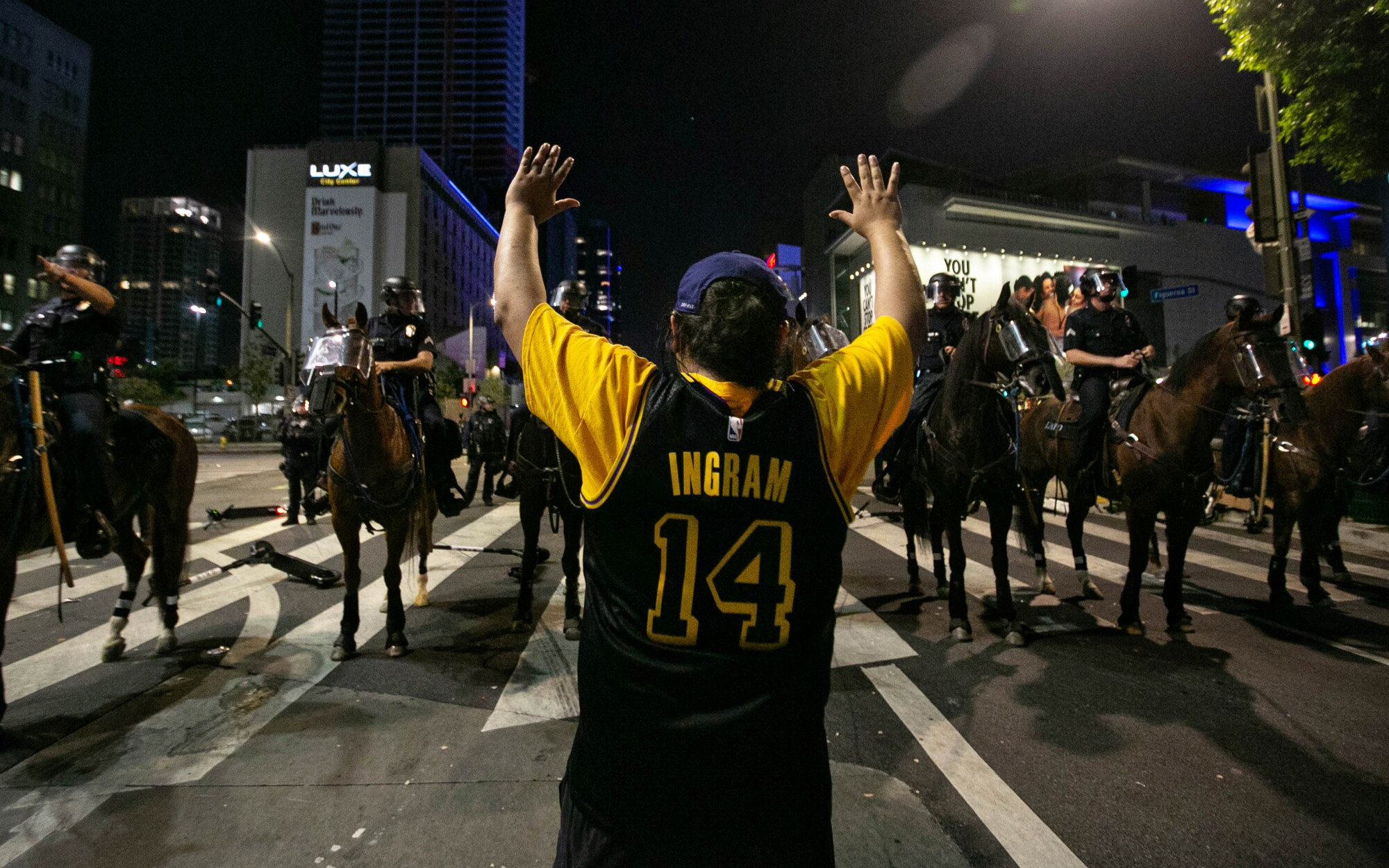 LAPD officers on horses clear the area near L.A. Live, declaring an unlawful assembly.