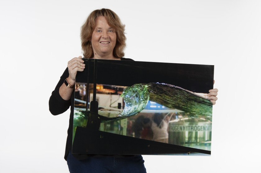 Kimberly Prather, distinguished professor and chair of atmospheric chemistry at Scripps Institution of Oceanography at UC San Diego, holds up a photo of an ocean wave created in the lab.