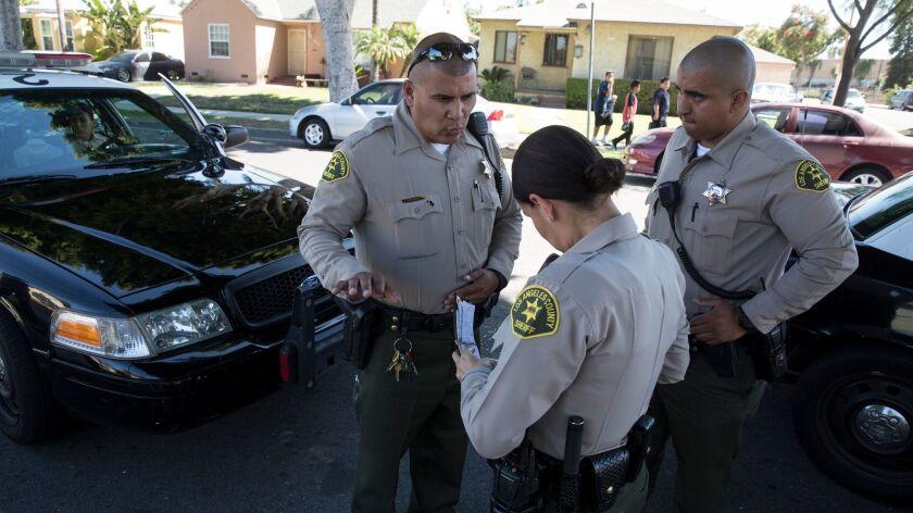 MAYWOOD, CALIF. -- TUESDAY, JUNE 27, 2017: Sheriff's deputy Marino Gonzalez, left, talks with deput