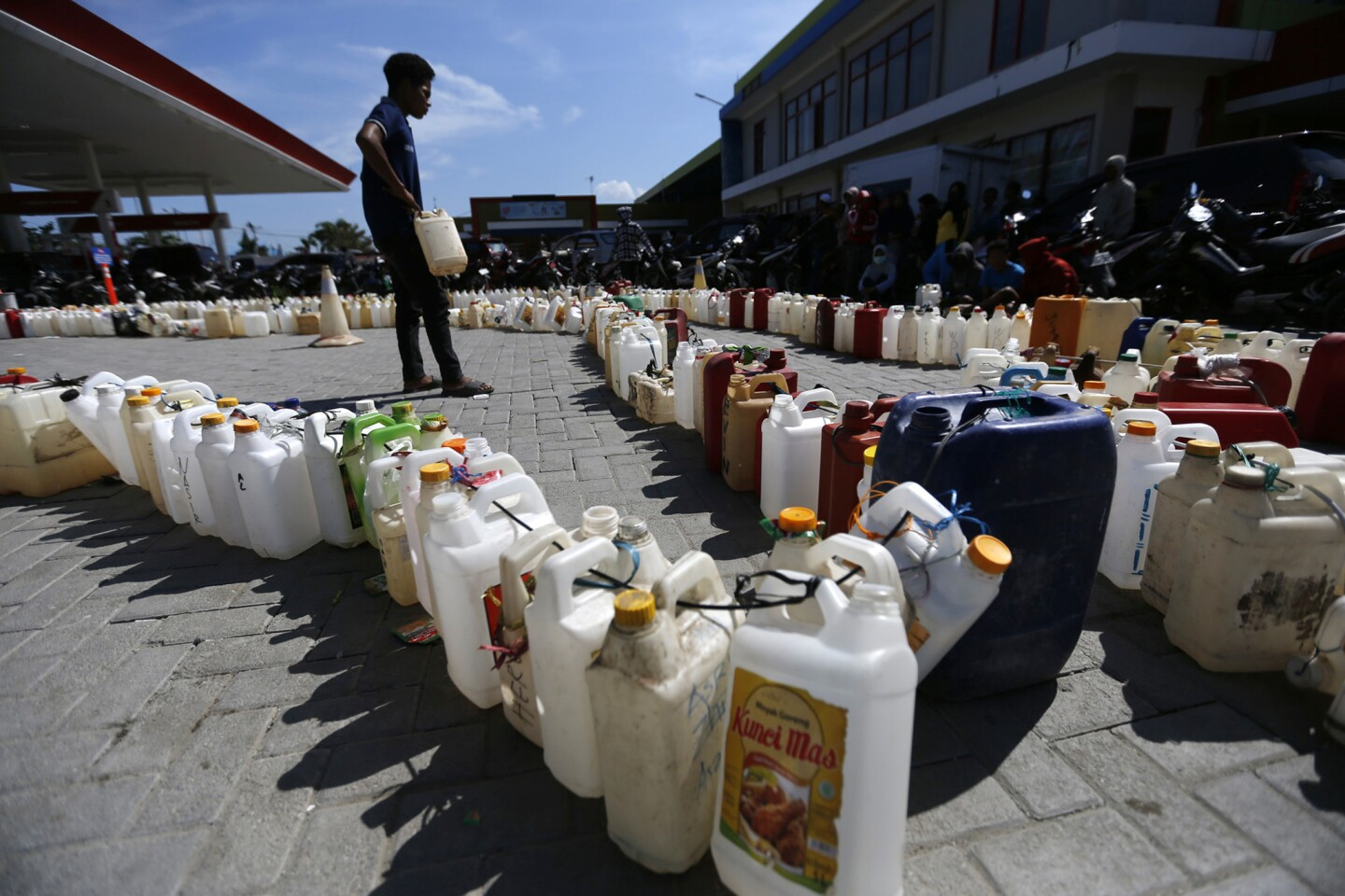A man looks over lines of containers as people queue up Friday at a gas station in Palu, Central Sulawesi, Indonesia.