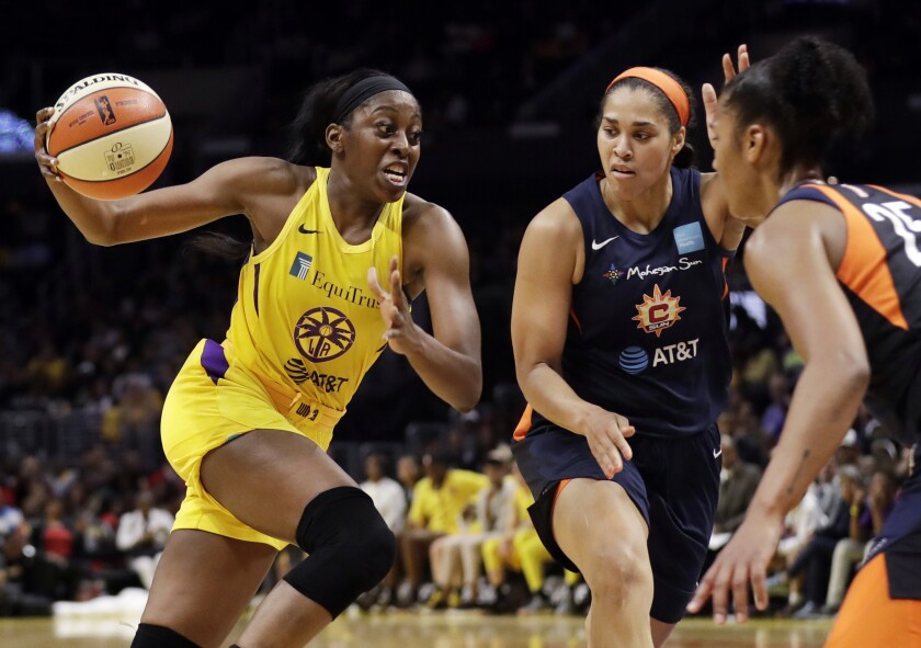 """FILE - In this May 31, 2019, file photo, Los Angeles Sparks' Chiney Ogwumike, left, dribbles next to Connecticut Sun's Brionna Jones, center, and Alyssa Thomas, right, during the second half of a WNBA basketball game in Los Angeles. Chiney Ogwumike is already one of sports busiest athletes as a WNBA player and ESPN Radio host. But the LA Sparks star forward added another accomplishment during the past year. She is the executive producer of """"144"""", which documents the league's 2020 season inside the bubble in Florida. (AP Photo/Marcio Jose Sanchez, File)"""