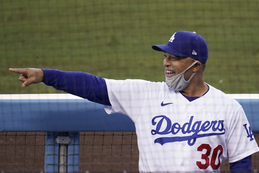 Dodgers manager Dave Roberts points in the dugout before a game.