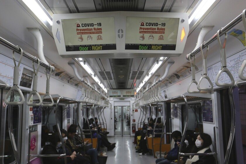 """Electric screens about precautions against the illness COVID-19 are seen in a subway train in Seoul, South Korea, Sunday, Feb. 23, 2020. South Korea's president said Sunday that he was putting his country on its highest alert for infectious diseases and ordered officials to take """"unprecedented, powerful"""" steps to fight a soaring viral outbreak. (AP Photo/Ahn Young-joon)"""