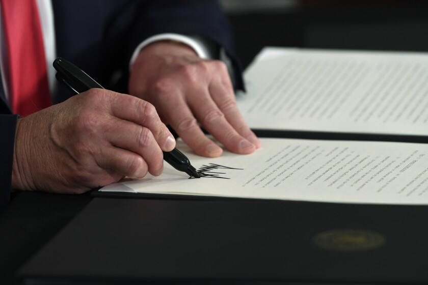 A close-up image of Trump's hands shows him signing an executive order