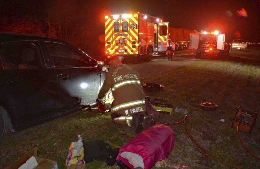 This photo provided by Colleton County Fire Rescue shows a member of the Colleton County, N.C., Fire-Rescue uses a tool to lift a woman's car Sunday, Feb. 2, 2020. The woman called 911 with her toes after her hands were crushed while changing a flat tire. (Colleton County Fire Rescue via AP)