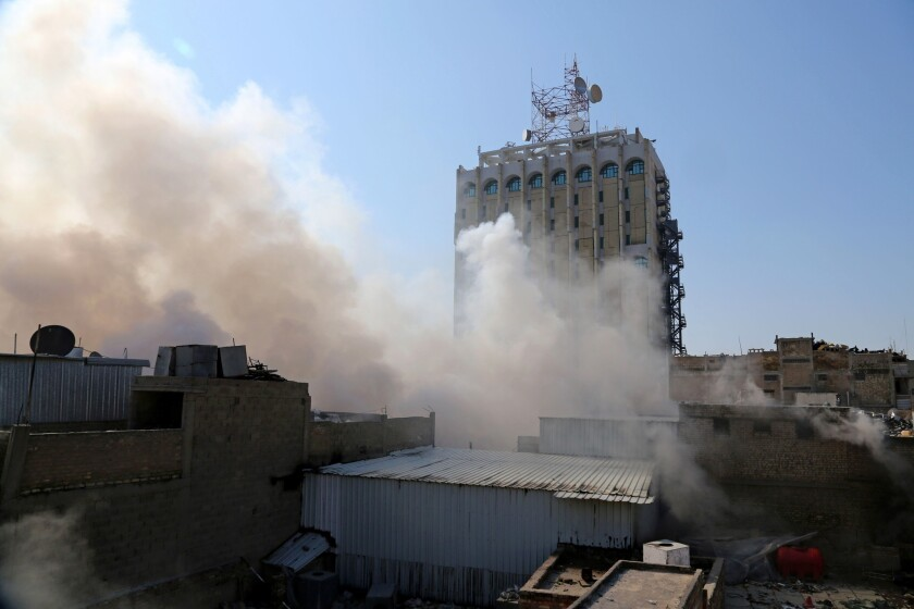 Smoke rises after a parked car bomb went off at a commercial center in central Baghdad.