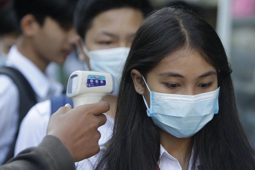 Estudiantes se revisan la temperatura, como medida preventiva por el coronavirus, al llegar a la escuela