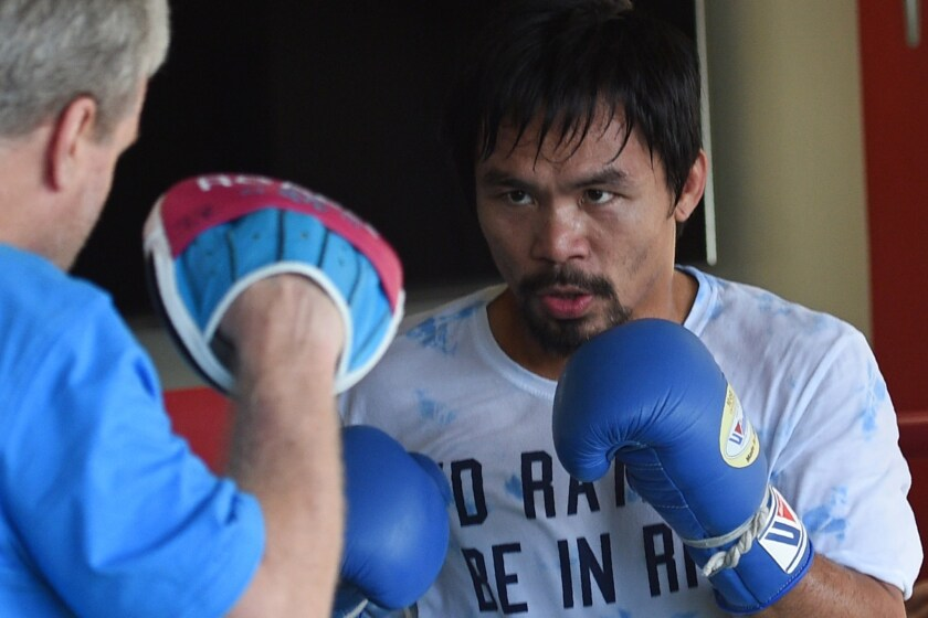 Manny Pacquiao spars with trainer Freddie Roach at a gym in General Santos, Philipppines, on Feb. 15.