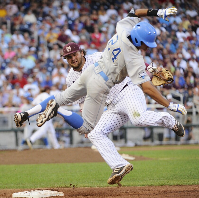 UCLA's Brian Carroll, right, and Mississippi State's Wes Rea collide a first base during the fourth inning of Game 1 of the College World Series on Monday.