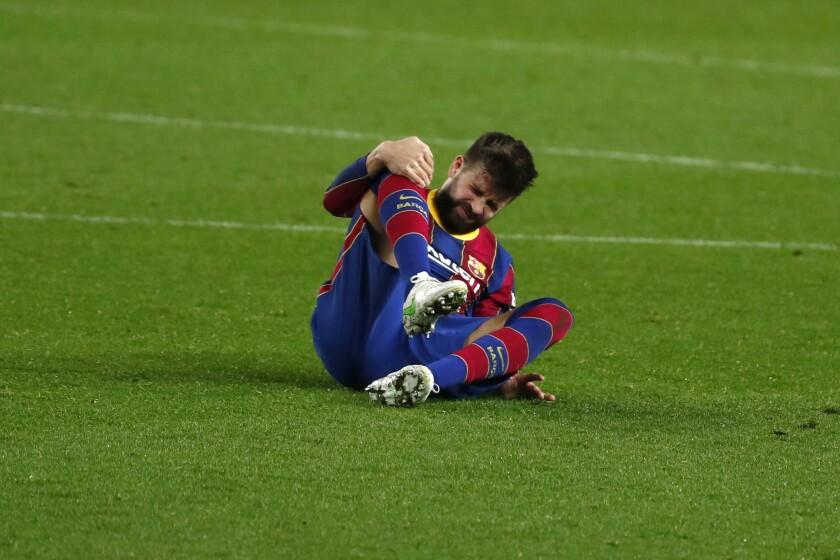 Barcelona's Gerard Pique holds his knee after getting injured during the the Copa del Rey semifinal, second leg, soccer match between FC Barcelona and Sevilla FC at the Camp Nou stadium in Barcelona, Spain, Wednesday March 3, 2021. (AP Photo/Joan Monfort)