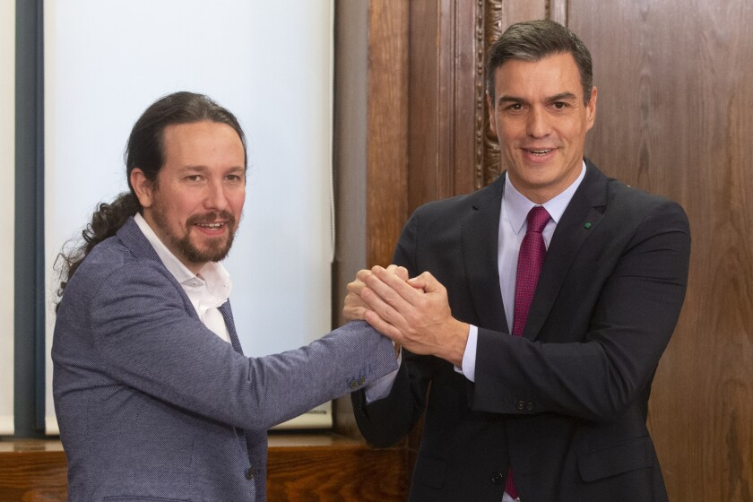 Spain's caretaker Prime Minister Pedro Sanchez, right and Podemos party leader Pablo Iglesias clasp hands after signing an agreement between the two parties in the Spanish parliament in Madrid, Spain, Monday, Dec. 30, 2019. Sanchez hopes to form center-left governing alliance to take office in the country in the coming days. (AP Photo/Paul White)