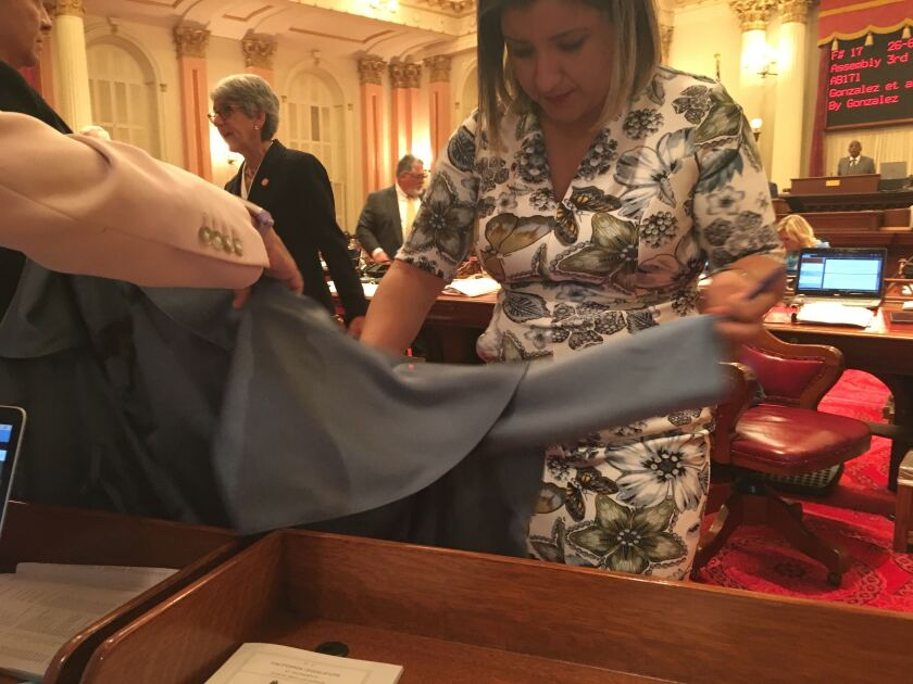 Sen. Melissa Hurtado (D-Sanger) inspects a jacket she was wearing just after it was splashed with a red liquid from a protester in the balcony of the Senate chambers.