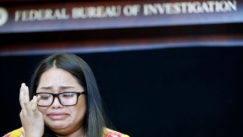 Dysabel Munguia cries as she speaks during a news conference to announce the addition of fugitive Je